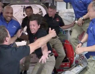 4-astronauts-float-into-the-international-space-station-and-open-arms